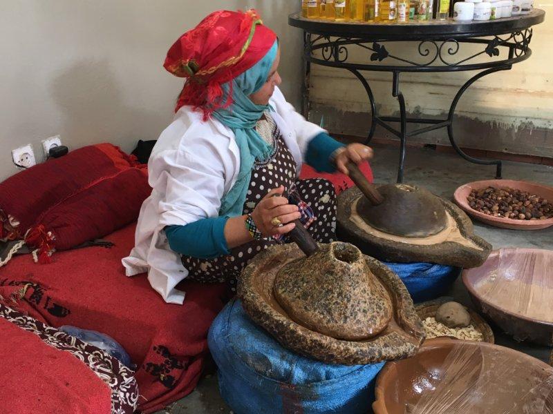 Moroccan woman grinding argan seeds