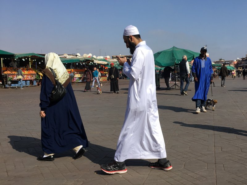 Man and his phone crossing Jemaa el-Fna