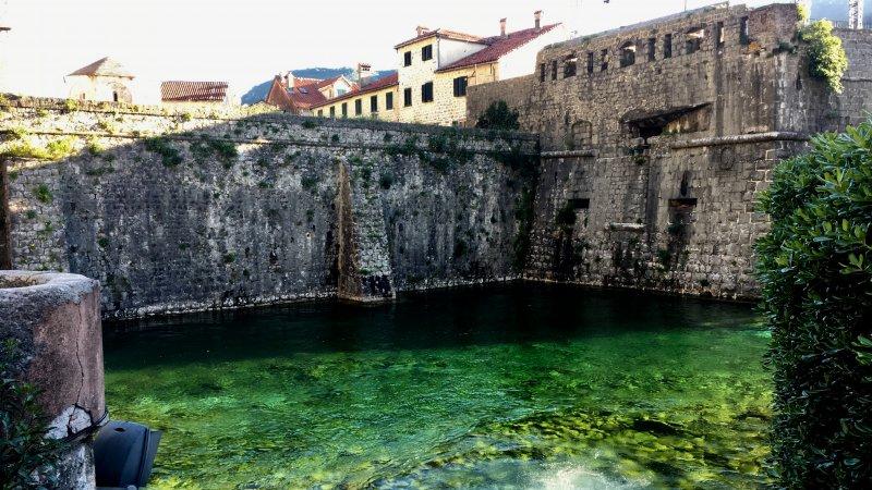 Kotor city wall and green water